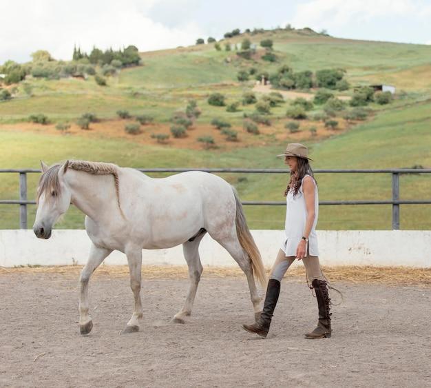 Женщина-фермер с лошадью на ранчо, вид сбоку