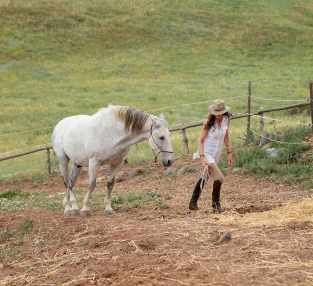 Вид сбоку женщины-фермера с лошадью на открытом воздухе