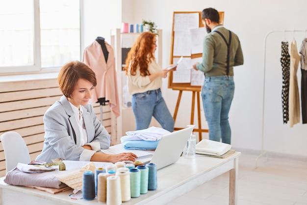 Вид сбоку модельера женского пола, работающего в ателье с коллегами и ноутбуком