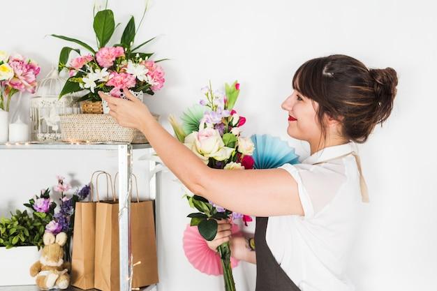 Вид сбоку женщины-флориста, глядя на свежие цветы на полке