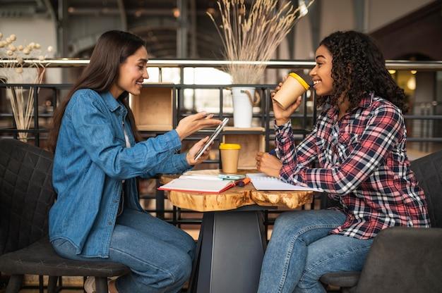 Вид сбоку подруги, делающей домашнюю работу в кафе, выпивая