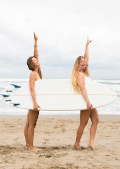Вид сбоку подруг, держащих доску для серфинга на пляже с копией пространства