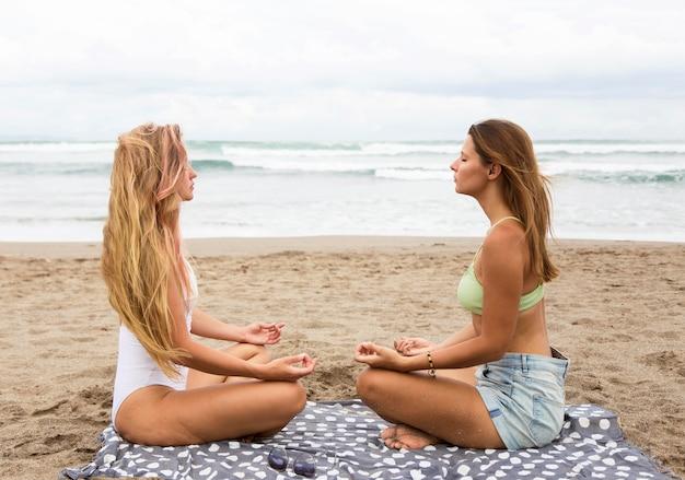 ビーチで瞑想する女性の友人の側面図