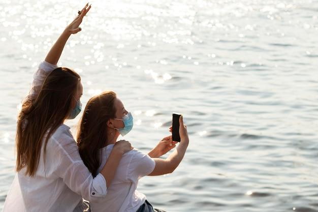 湖のほとりで自分撮りをしているフェイスマスクを持つ女性の友人の側面図