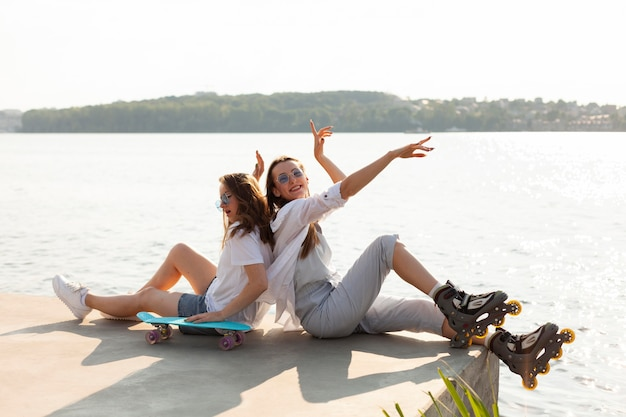 湖のそばでスケートボードとローラーブレードを持つ女性の友人の側面図