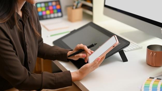사무실 책상에 앉아있는 동안 스마트 폰을 사용하는 여성 그래픽 디자이너의 측면보기