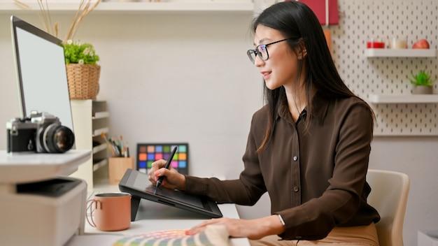 Вид сбоку женского графического дизайнера, работающего на компьютере и графическом планшете в удобной офисной комнате