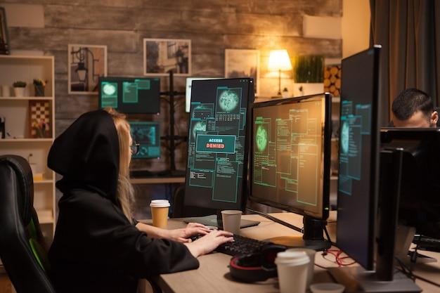 Вид сбоку на женщину-хакера в толстовке с капюшоном, закрывающую лицо, во время кражи информации из брандмауэра.