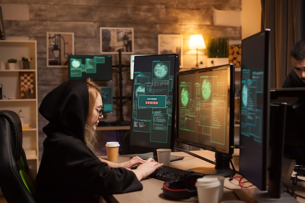 Вид сбоку на женщину-хакера, пишущую опасное вредоносное по с использованием современного программного обеспечения.