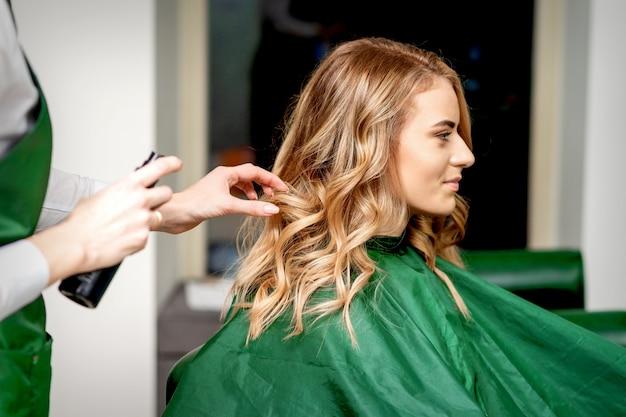 헤어 살롱에서 고객의 여성 머리카락을 고정하는 헤어 스프레이를 사용하는 여성 미용사의 측면보기