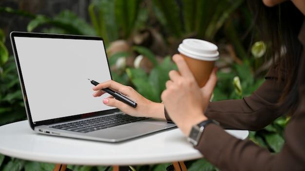 紙コップを持って、カフェでラウンド物語でラップトップで作業している女性の手の側面図