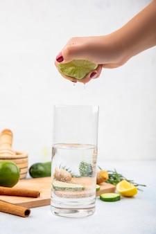 Вид сбоку женской руки, сжимая свежий лимон в стакан воды на белой поверхности