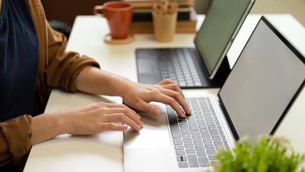 Вид сбоку женской руки, печатающей на клавиатуре ноутбука на офисном столе с другим ноутбуком и канцелярскими принадлежностями