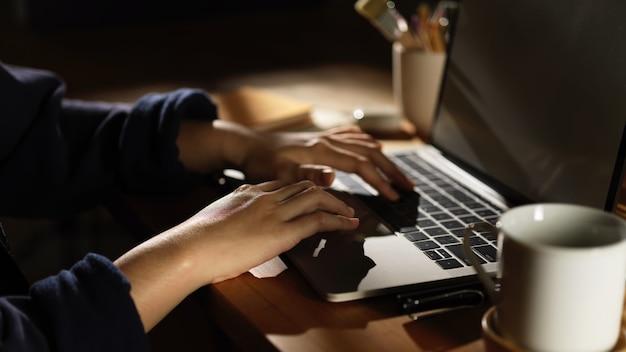 コーヒーカップと木製のテーブルの上のラップトップで入力する女性の手の側面図