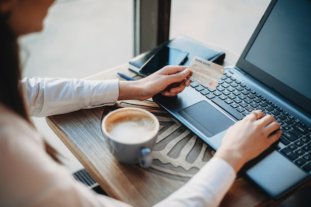 플라스틱 골드 신용 카드를 들고 커피 숍에 앉아있는 동안 노트북을 사용하는 여성 손의 측면보기. 온라인 뱅킹 개념. 온라인 쇼핑 개념.