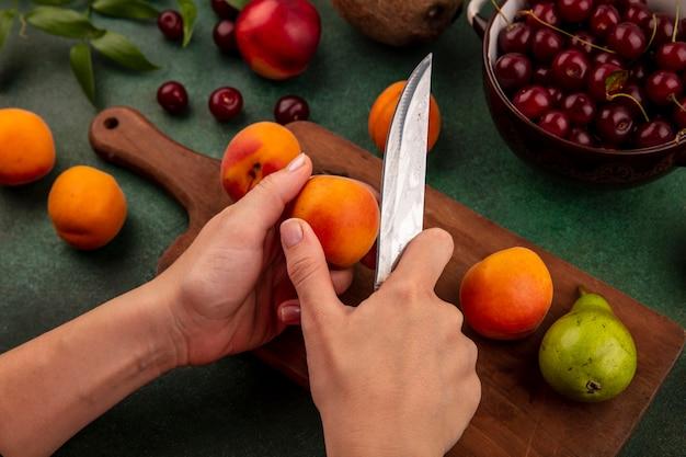 まな板の上にナイフと梨でアプリコットをスライスし、緑の背景に桃ココナッツと葉とボウルにさくらんぼをスライスする女性の手の側面図