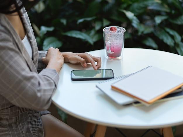Вид сбоку женских рук, трогающих смартфон на журнальном столике с напитком и ноутбуком в кафе