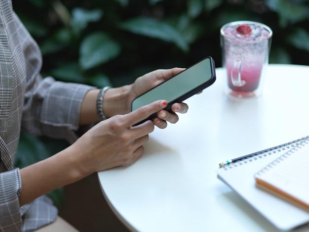Вид сбоку женских рук, использующих смартфон на журнальном столике с напитком и ноутбуком в кафе