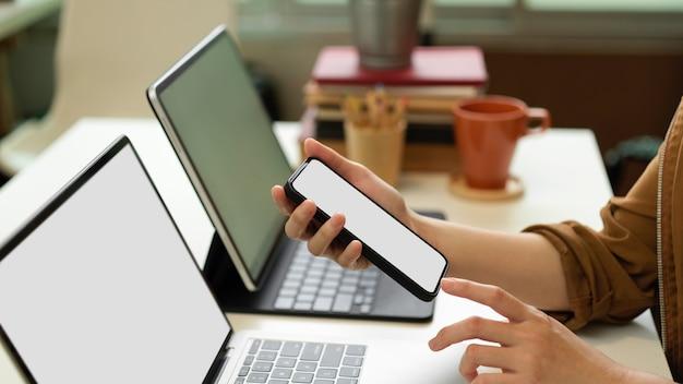 Вид сбоку женских рук, использующих смартфон, сидя за офисным столом с двумя ноутбуками, книгами и канцелярскими принадлежностями