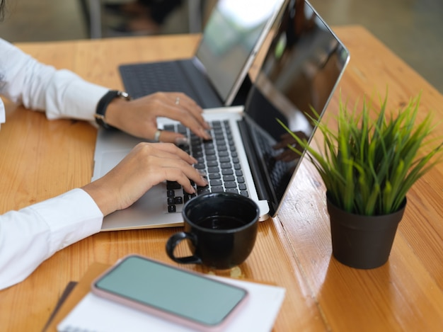 Вид сбоку женских рук, работающих с ноутбуком, планшетом, смартфоном и документами на деревянном столе