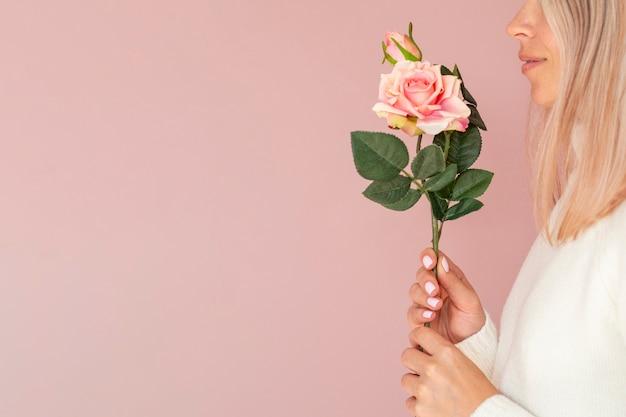 バラを保持している女性の側面図