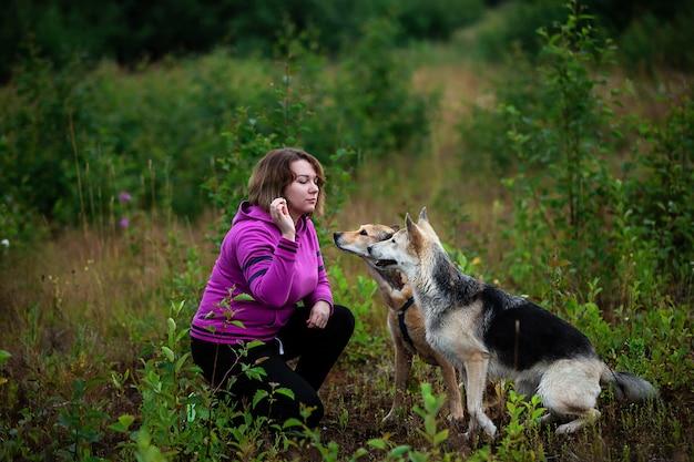 Самка в яркой толстовке с капюшоном тренирует послушных собак, проводя время в зеленом поле, вид сбоку