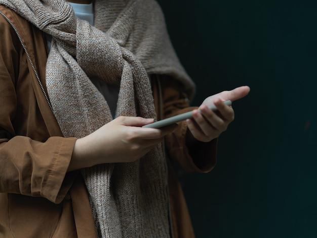 Вид сбоку женщины в свитере, использующей смартфон, стоя на темном фоне