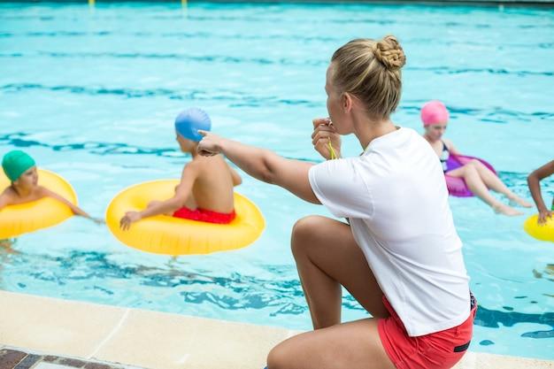 수영장에서 아이들을 가르치는 동안 휘파람 여성 인명 구조 원의 측면보기