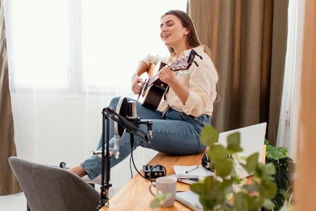 Женщина-музыкант дома играет на акустической гитаре и поет, вид сбоку