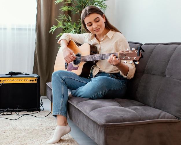 Вид сбоку женщины-музыканта дома, играющего на акустической гитаре, сидя на диване