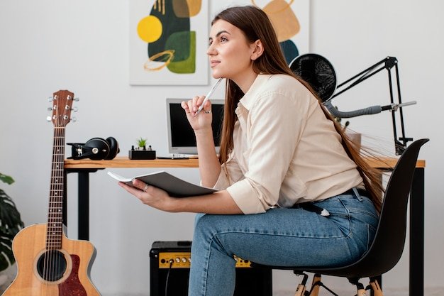 Женщина-музыкант дома пишет песню, вид сбоку