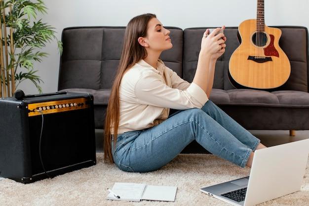 Женщина-музыкант, держащая кружку рядом с акустической гитарой, вид сбоку