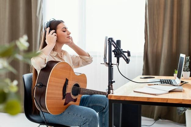 Вид сбоку на женщину-музыканта, играющую на акустической гитаре и готовящуюся записать песню дома