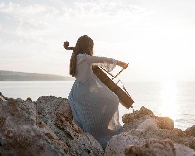 Вид сбоку женского музыканта, играющего на виолончели на закате на скалах