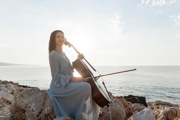 岩の上で海のそばでチェロを演奏する女性ミュージシャンの側面図