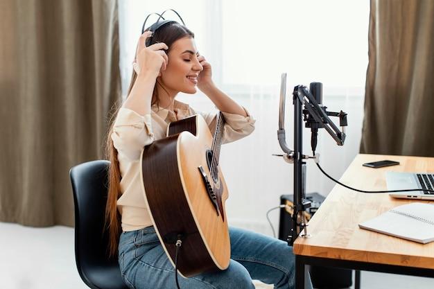 Вид сбоку девушки-музыканта, надевающего наушники для записи песни и игры на акустической гитаре