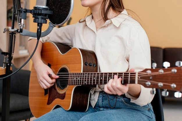 Вид сбоку женского музыканта, записывающего песню и играющего на акустической гитаре дома