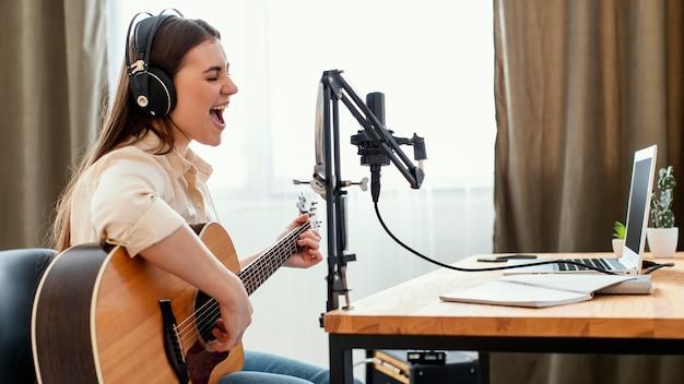 어쿠스틱 기타를 연주하는 동안 집에서 노래를 녹음하는 여성 음악가의 측면보기