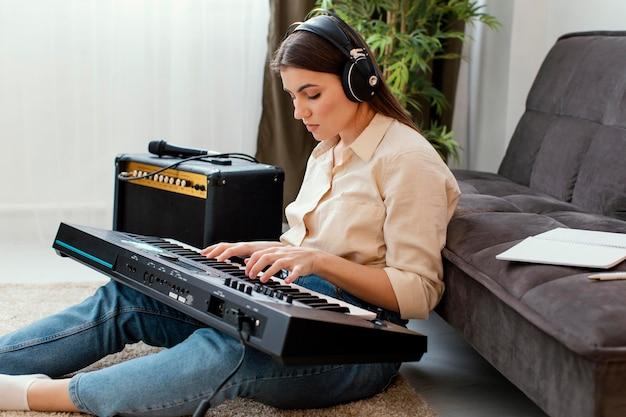 피아노 키보드를 연주하는 헤드폰으로 여성 음악가의 측면보기