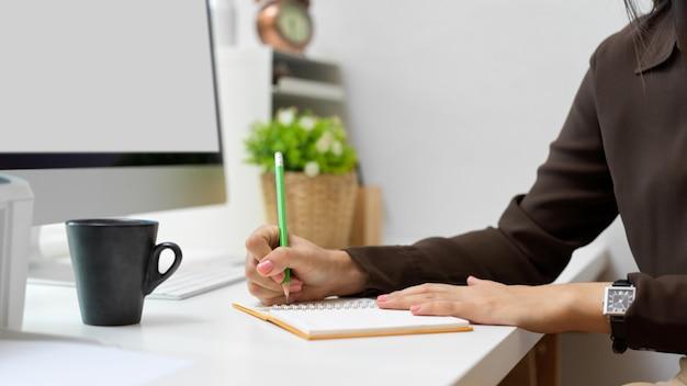 컴퓨터 테이블에 노트북에 쓰는 여성 회사원 손의 측면보기