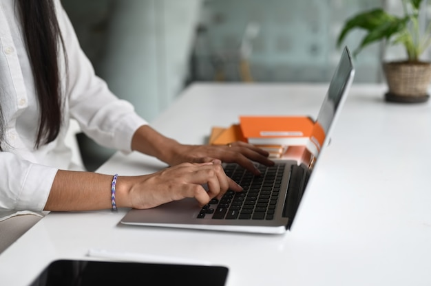 Вид сбоку женского офисного работника, работающего на ноутбуке в современном офисе.
