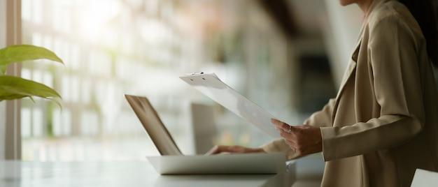Женский офисный работник, работающий с ноутбуком и оформлением документов на столе в офисе со стеклянной стеной, вид сбоку