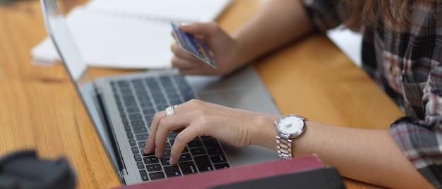 Вид сбоку женских покупок в интернете и онлайн-платежей с помощью кредитной карты на ноутбуке