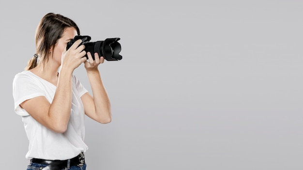 Вид сбоку женского фотографа с копией пространства