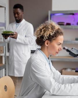 현미경 및 남성 동료와 함께 실험실에서 여성 연구원의 측면보기