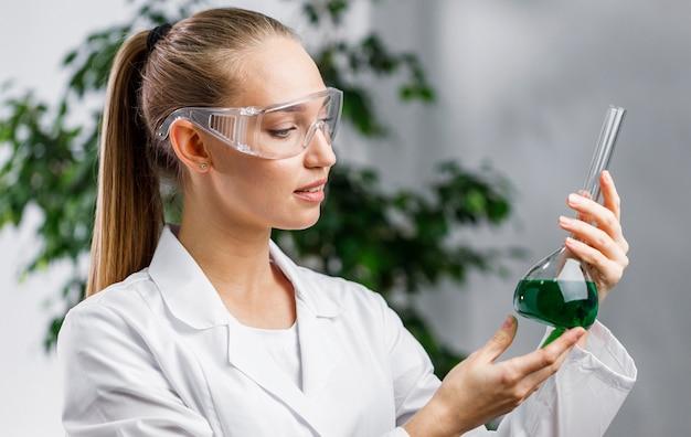 테스트 튜브와 안전 안경 여성 연구원의 측면보기