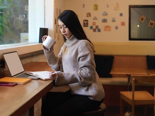 カフェの木製カウンターバーで作業しながらホットドリンクを飲むと休んでいる女性の側面図