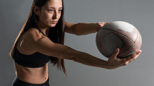공 포즈 여성 럭비 선수의 측면보기 무료 사진