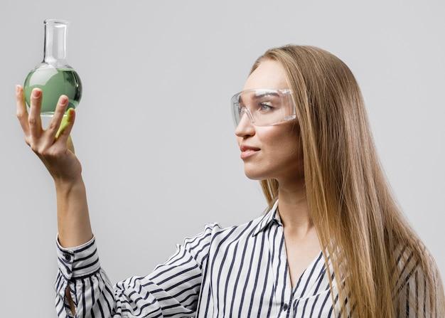 안전 안경을 착용하는 동안 테스트 튜브를 들고 여성 과학자의 측면보기