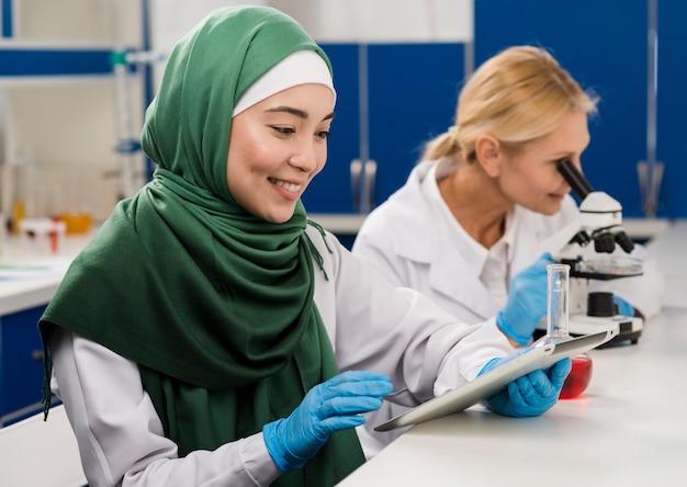 Вид сбоку женщин-ученых в лаборатории, работающих вместе